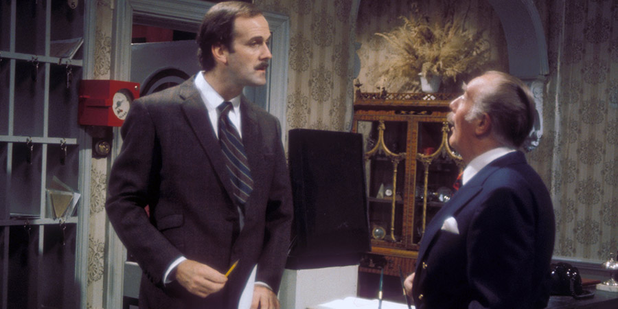 Fawlty Towers. Image shows from L to R: Basil Fawlty (John Cleese), Major Gowen (Ballard Berkeley). Copyright: BBC.