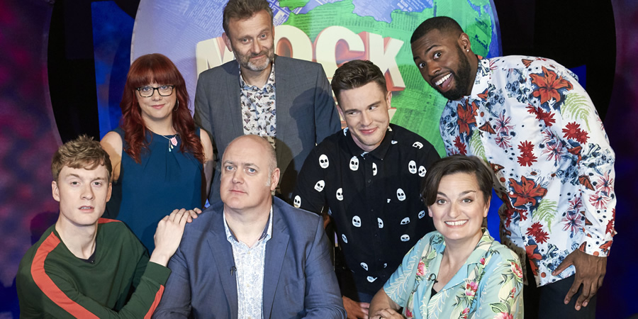 Mock The Week. Image shows from L to R: James Acaster, Angela Barnes, Hugh Dennis, Dara O Briain, Ed Gamble, Darren Harriott, Zoe Lyons. Copyright: Angst Productions.