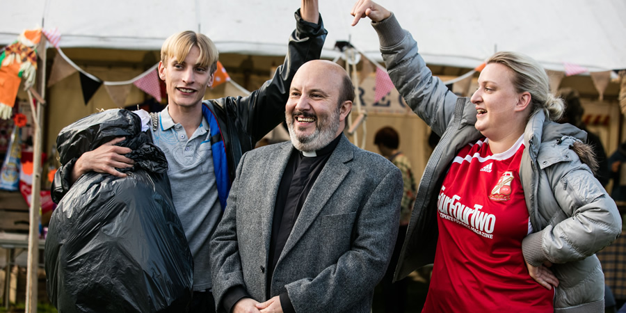This Country. Image shows from L to R: Lee 'Kurtan' Mucklowe (Charlie Cooper), Reverend Francis Seaton (Paul Chahidi), Kerry Mucklowe (Daisy May Cooper). Copyright: BBC.