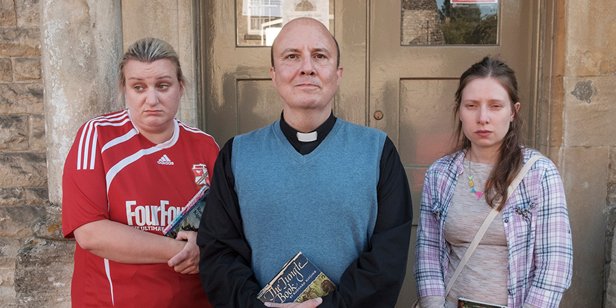 This Country. Image shows from L to R: Kerry Mucklowe (Daisy May Cooper), Reverend Francis Seaton (Paul Chahidi), Kayleigh Hudson (Celeste Dring).