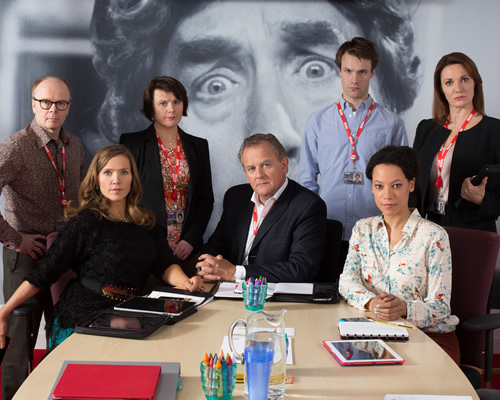 W1A. Image shows from L to R: Simon Harwood (Jason Watkins), Siobhan Sharpe (Jessica Hynes), Tracey Pritchard (Monica Dolan), Ian Fletcher (Hugh Bonneville), Will Humphries (Hugh Skinner), Lucy Freeman (Nina Sosanya), Anna Rampton (Sarah Parish). Image credit: British Broadcasting Corporation.